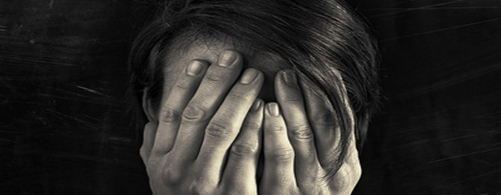 Concept of fear, domestic violence. Woman covers her face her hands. Dim light and black, scratched background  creates a dramatic mood of this black and white image.